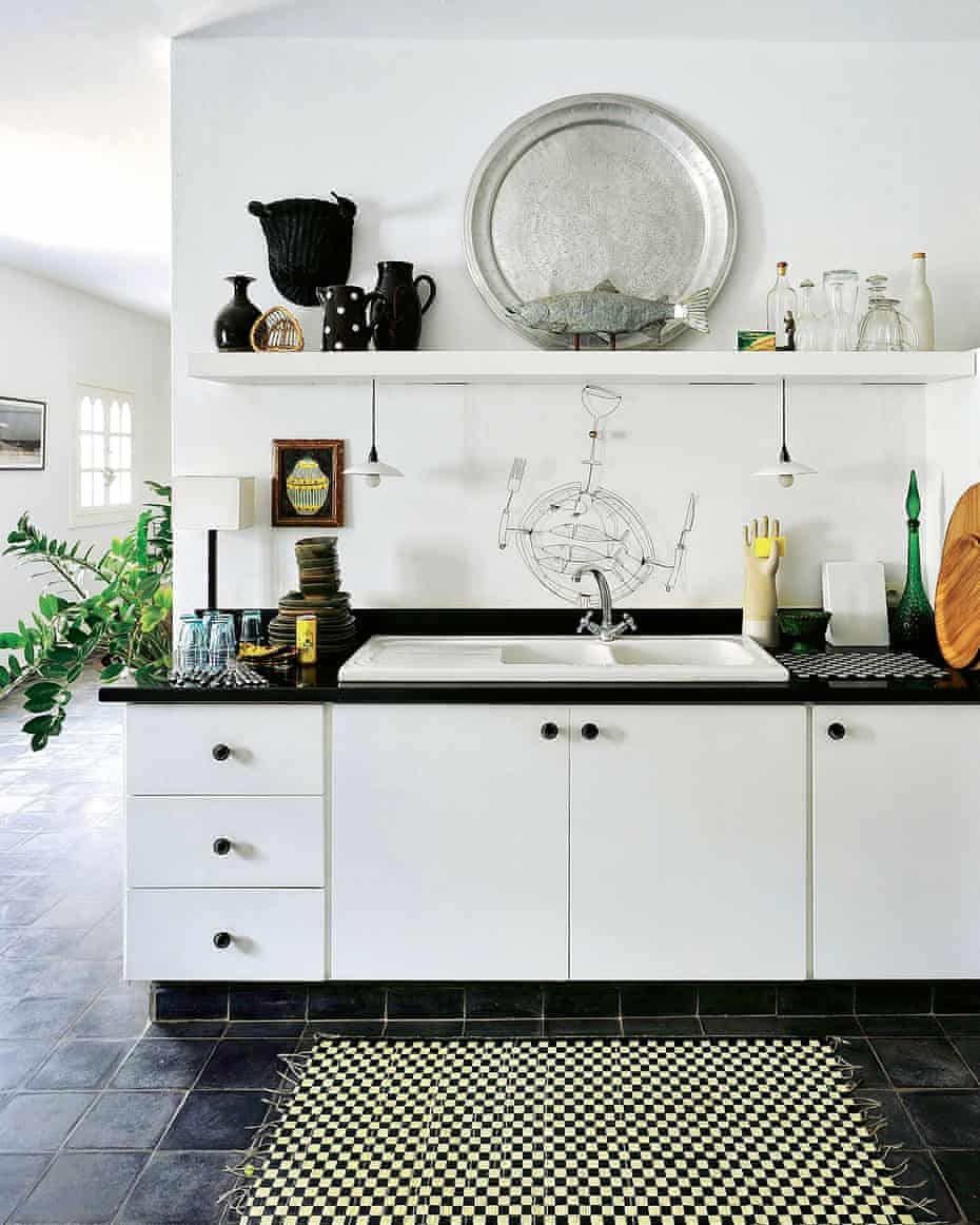 The kitchen features simple white cabinets with black worktops, made by local carpenters. Henon found the large aluminium platters in Marrakech (try moroccanbazaar.com for similar).