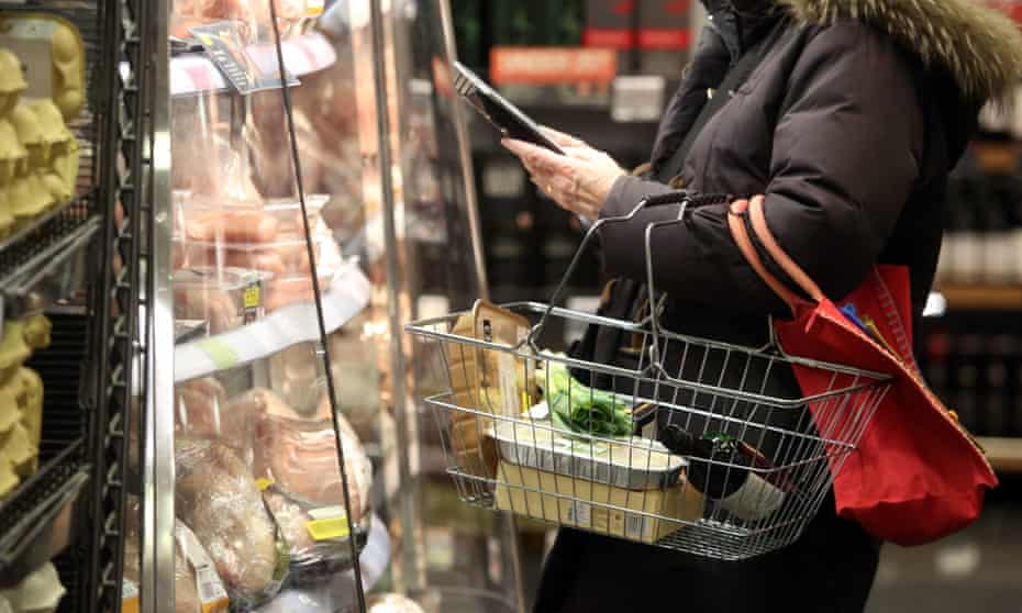 A customer browses products at a chilled fresh food cabinet inside a branch of Marks & Spencer.