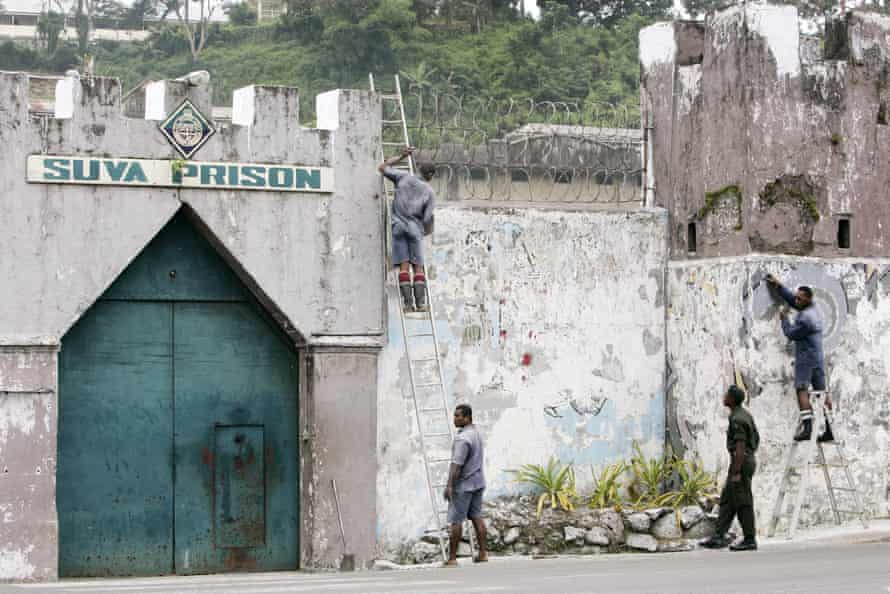 Inmates are watched by a guard, second,from right, as they work to strip a painted mural from the wall of the Suva Prison in the Fijian capitol.