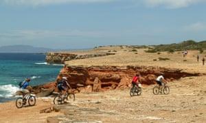 Mountain Bikers riding along a coastal path.