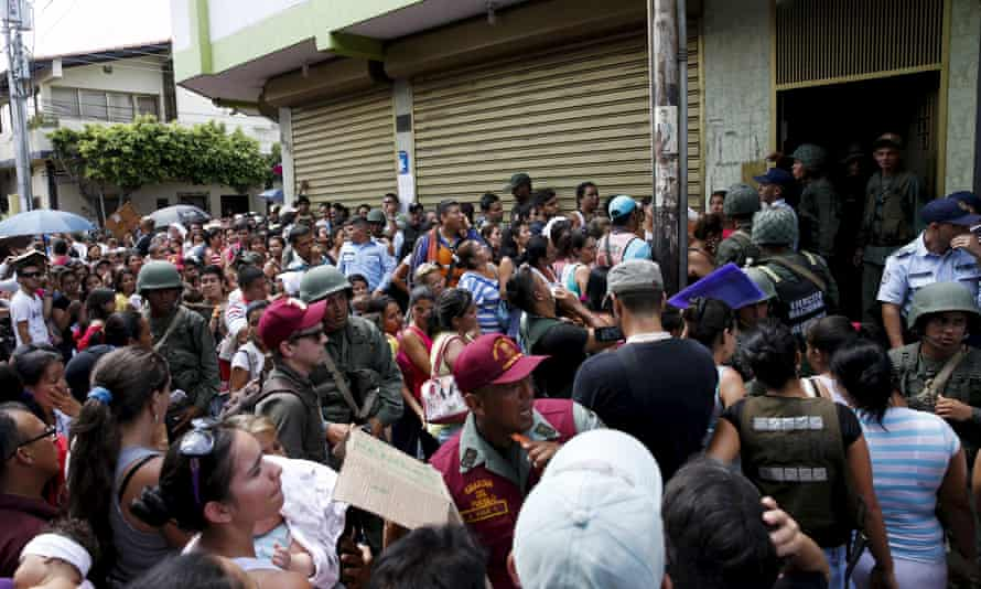 Venezuelan soldiers try to control the crowd queueing outside a supermarket while trying to buy staple items