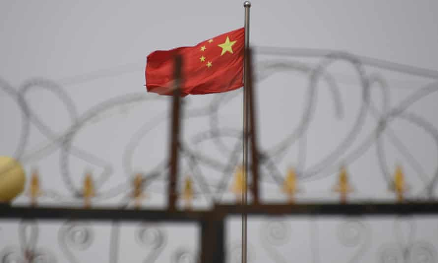 A picture taken in June 2019 shows the Chinese flag behind razor wire at a housing compound in Yangisar, in China's Xinjiang region