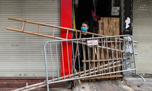A woman looks out from behind an improvised barricade made of wooden planks and a ladder to restrict residents' movements in Hanoi, as part of the authorities' plan to stop the spread of the Covid-19 coronavirus.