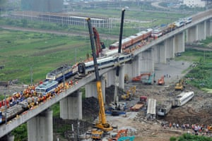 Workers clearing wreckage after a Chinese high-speed train derailed on 24 July, 2011 when it was hit from behind by another train near the city of Wenzhou in China's eastern Zhejiang province.