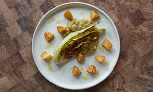 A wedge of seared green cabbage on a round plate with split pea cubes