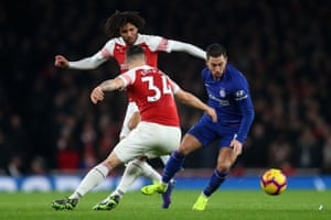 Eden Hazard of Chelsea runs with the ball under pressure from Arsenal's Mohamed Elneny and Granit Xhaka.