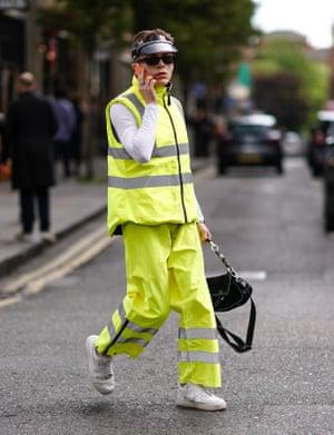 A model walks across a road wearing hi-vis during the London men's fashion week