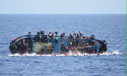 Migrants in an overcrowded boat, which was about to capsize, are rescued by the Italian Navy