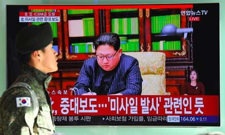 A South Korean soldier walks past a television news screen showing North Korean leader Kim Jong-Un in Seoul on 29 November 2017.