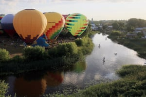 Suzdal, Russia. Paddleboarders look at the hot air balloons as they pass the Golden Ring balloon festival near Ilyinsky meadow