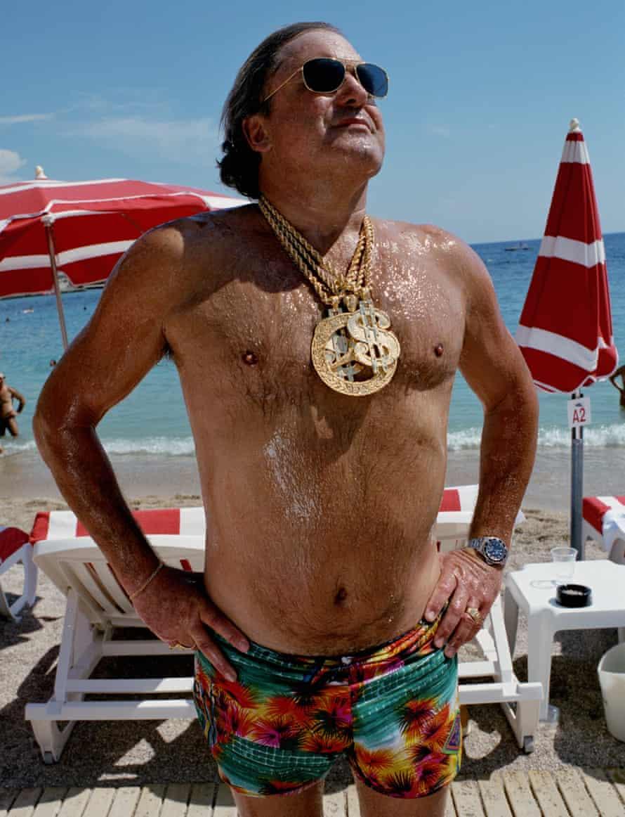 Man on beach wearing medallions