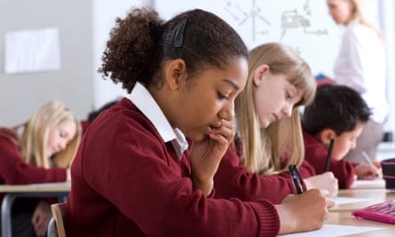 Students taking test in classroom, Bristol, UK