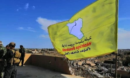 The yellow flag of US-backed Syrian Democratic Forces in the village of Baghuz, Syria