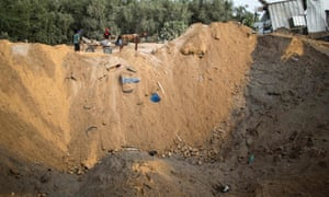 Palestinian militants inspect a crater in northern Gaza