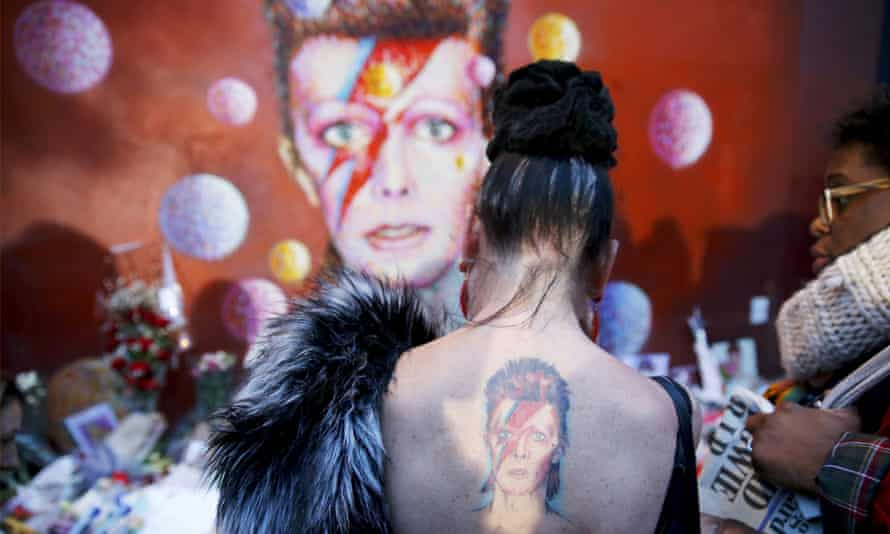 A woman with a Ziggy Stardust tattoo visits a mural of David Bowie in Brixton.