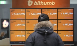 a man watches screens showing cryptocurrency values in an exchange in seoul south korea