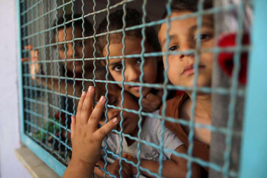 Palestinian children, who fled their homes due to Israeli air and artillery strikes, look through a window fence at a United Nations-run school where they take refuge, in Gaza City.