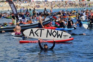 Protesters take part in a paddle out, organised by Surfers Against Sewage, on Gyllyngvase Beach.