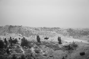 A light dusting of snow covers the North Dakota Badlands as a lone rider patrols a butte in search of stray cows and calves.