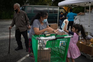 Amber, 5, helps her grandmother Minerva Delgado load groceries distributed by the Wesley Community Center to residents affected by the economic fallout caused by the coronavirus outbreak in Houston, Texas, US, on 24 July 2020.