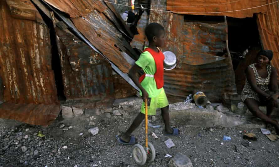 A boy walks among makeshift shelters at La Saline neighbourhood in Port-au-Prince, Haiti