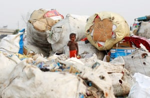 New Delhi, India A boy stands on a sack of discarded plastic goods at a recycling yard.