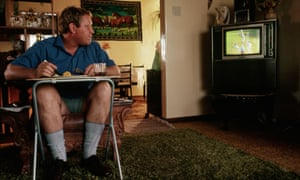 Man eating lunch watching cricket on Television