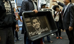 Aids activists carry an image of Turing Pharmaceuticals CEO Martin Shkreli in a makeshift cat litter pan.