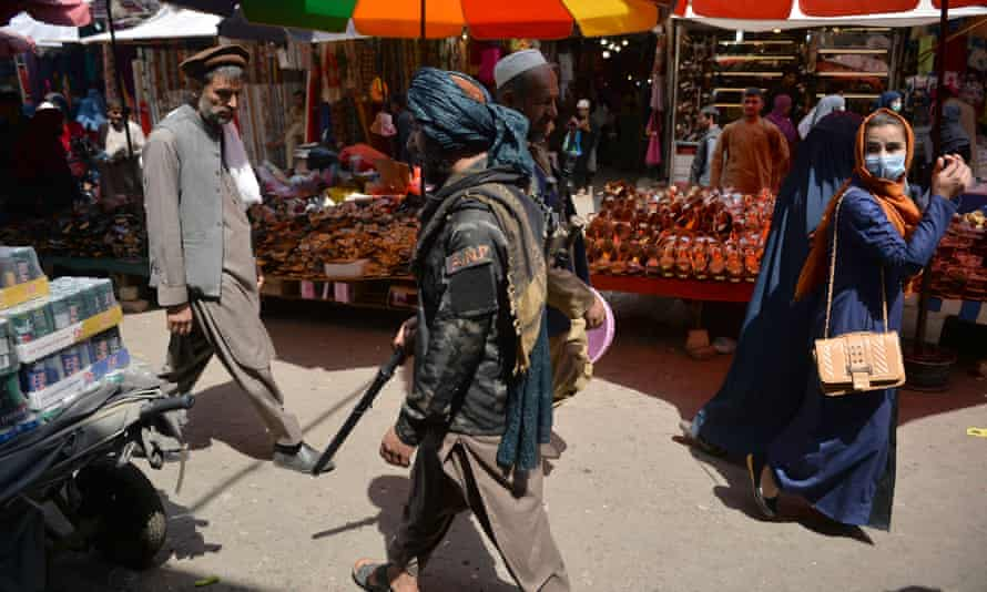 A Taliban fighter walks past shoppers in Mandawi market in Kabul, 1 September 2021