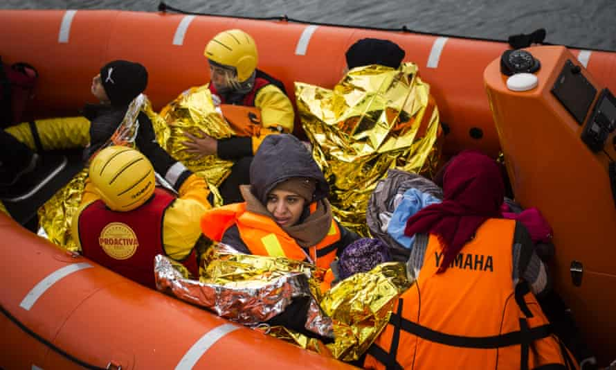 Refugees and migrants onboard a dinghy approach the Greek island of Lesbos