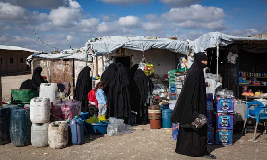 Women shop in a makeshift market inside al-Hawl camp in Syria