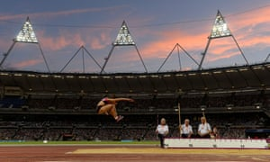 A woman in mid-air as she does the triple jump while three judges look on at the Olympic Stadium in London