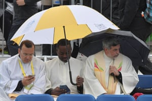 Members of the clergy shelter from the rain at Phoenix Park in Dublin