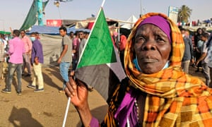 A Sudanese woman holds a national flag during a demonstration in front of the military headquarters in Khartoum