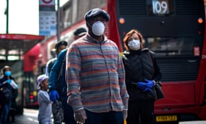 People wearing face masks as a precaution against coronavirus wait in line for a supermarket in Brixton, South London.