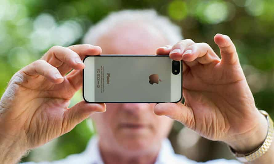 Senior man taking a photo with an Apple iphone