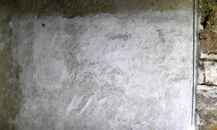 Graffiti written in pencil on the wall besides the bricked-up passageway.