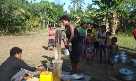 People line up to collect water in plastic containers and cooking pots from a communal pump in a rural community in Madang Province, Papua New Guinea.