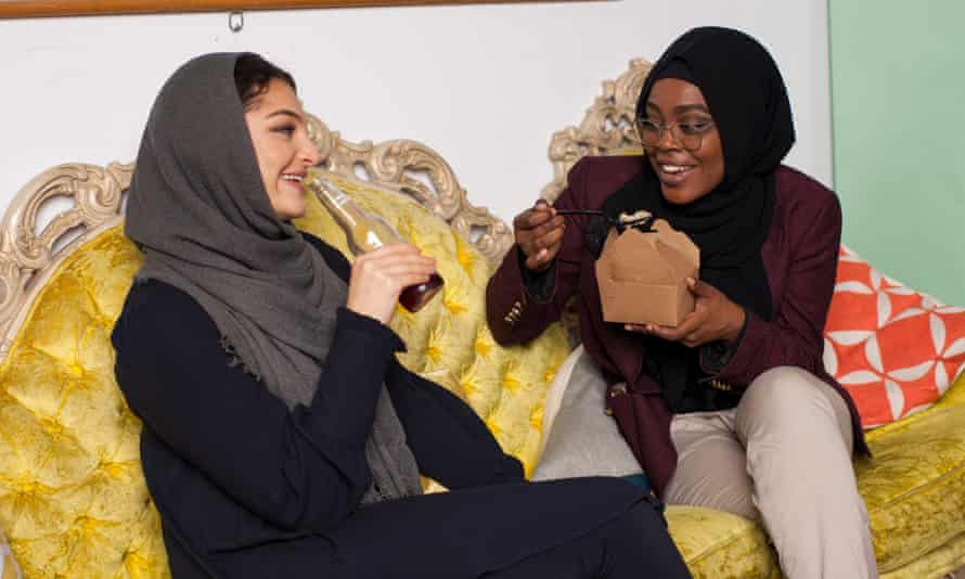 Young Muslim women eating takeaway and drinking soft drink in a home