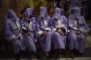 Masked penitents rest inside a church after taking part in a procession in Siétamo, Aragon