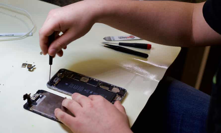 File photo of a technician treating a water-damaged iPhone