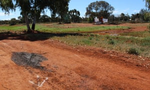 The patch of oil marking where the Nissan Navara came to rest, looking back across Gribble Creek Reserve toward Clancy Street and a tree that had been set up as a memorial to Elijah Doughty.