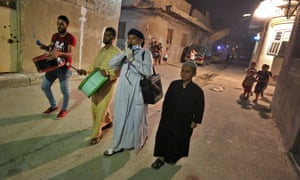 """In this file photo taken on 7 May 2020 Sayyed Mozahem, the """"Musaharati"""" (2-R), as he calls for Muslims to have their final meal before a new day of fasting begins with the sunrise, in a small neighbourhood of the Iraqi capital Baghdad."""