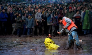 A festival-goer offers a cigarette to a man in a high vis suit who sits in a puddle of mud as a crowd watches the action on stage.