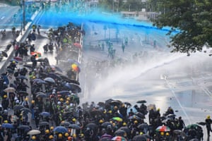 Pro-democracy protesters react as police fire water cannon outside the government headquarters