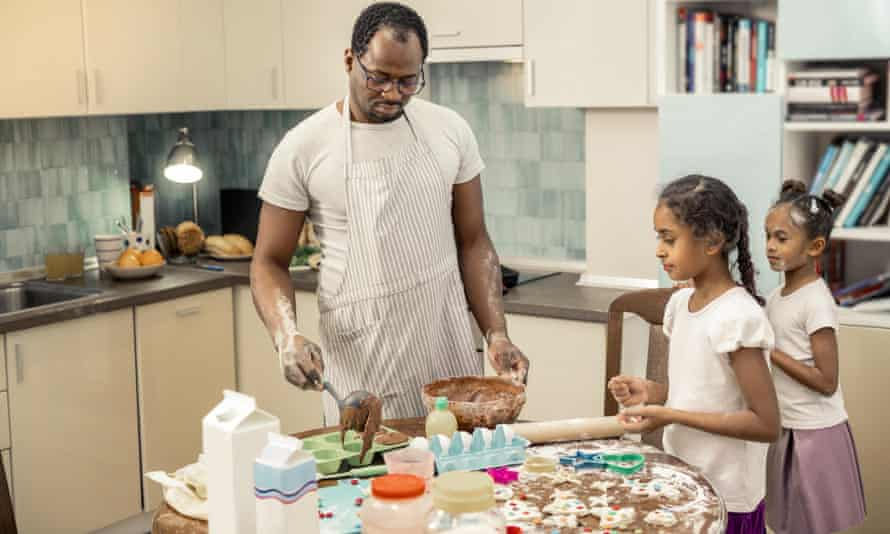 Father making cupcakes with children.