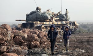 Two boys walk by Turkish army tanks in Afrin, Syria