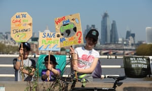 Young protesters hold placards on Waterloo Bridge on Sunday