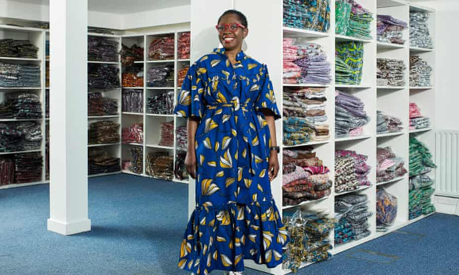Yvonne Telford wearing a full-length blue-patterned dress, pictured in her warehouse with shelves of her clothing behind her
