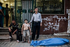 'His father had gone, and he didn't quite understand that' … Ahmed, 12, waits with his uncle by the body of his father who was killed by a shell in Aleppo, Syria. Ahmed was also injured in the back by shrapnel.